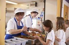 Deux femmes servant la nourriture à une fille dans une file d'attente de cafétéria de l'école Images stock