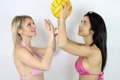 Deux femmes sexy jouant le volleyball de plage Image libre de droits