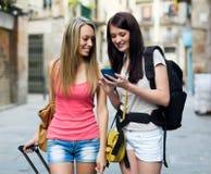 Deux femmes souriant avec le bagage et employant la carte Images libres de droits