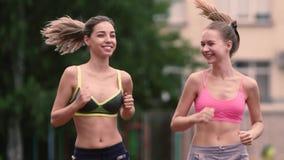 Deux femmes sportives courantes d'amis de forme physique de femmes pulsant dans la ville urbaine clips vidéos