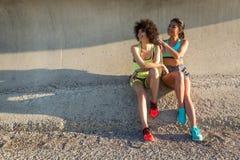 Deux femmes sportives heureuses dans les vêtements de sport se reposant ensemble Images libres de droits