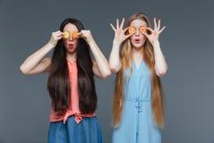 Deux femmes stupéfaites drôles ont couvert leurs yeux de sucreries de confiture d'oranges Image libre de droits