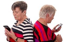 Deux femmes supérieures lisant SMS Image libre de droits