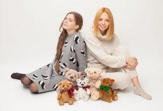 Deux femmes sur un fond blanc avec les jouets mous soutient Photographie stock