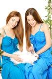 Deux femmes sur une oscillation sur le fond blanc Photo stock