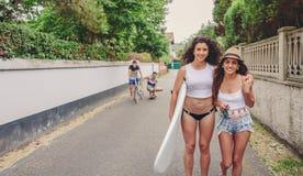 Deux femmes tenant la planche de surf et regardant l'appareil-photo Image stock