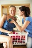 Deux femmes triant la blanchisserie dans la cuisine Image libre de droits