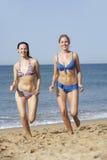 Deux femmes utilisant des bikinis fonctionnant le long de la plage Photo libre de droits