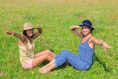 Deux femmes utilisant des chapeaux saluant dans le pré vert Image stock