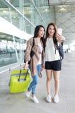 Deux femmes vont voyage et prenant le selfie dans l'aéroport Photos stock