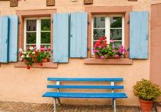 Deux fenêtres avec les abat-jour bleus sur un mur rose et un banc bleu Photo libre de droits