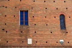 Deux fenêtres et manteaux des bras sur un mur antique Images libres de droits