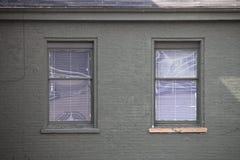 Deux fenêtres semblables sur le mur de briques gris Image stock