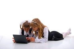 Deux fille et ordinateur portatif de pose. image stock