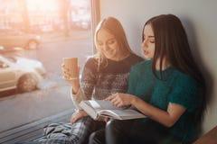 Deux fille s absorbée dans le livre de lecture pendant la coupure en café Les belles jeunes femmes mignonnes sont livre et boire  Photo stock
