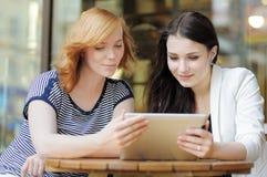 Deux filles à l'aide de la tablette Image libre de droits
