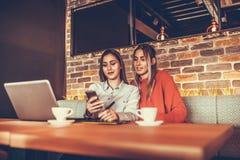 Deux filles à l'aide du smartphone Photos stock
