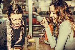 Deux filles à l'aide du smartphone et buvant du café Photo stock