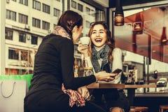 Deux filles à l'aide du téléphone portable et buvant du café Photos libres de droits
