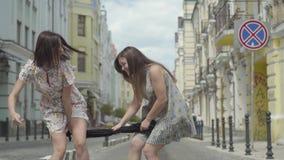 Deux filles à la mode tenant la robe noire et la tirant à leurs côtés sur la rue Concept d'achats banque de vidéos