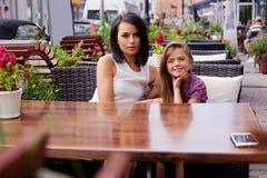 Deux filles à la table dans un café d'air ouvert Photographie stock libre de droits