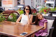 Deux filles à la table dans un café d'air ouvert Images stock