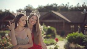 Deux filles étonnantes dans longues robes et couronnes banque de vidéos