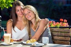 Deux filles étreignant en café extérieur Photographie stock libre de droits