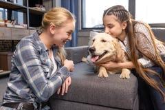 Deux filles étreignant le chien de golden retriever sur le sofa à la maison Images stock
