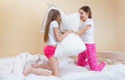 Deux filles actives riant tout en combattant avec des oreillers Photos libres de droits