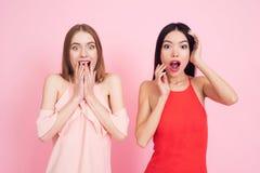 Deux filles agissant étonnées sur le fond rose célébrant femmes jour le 8 mars photos libres de droits