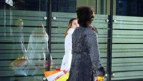 Deux filles après que faisant des emplettes descendiez la rue closeup banque de vidéos
