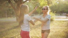 Deux filles arrosent l'amusement coloré de poudre et de avoir clips vidéos