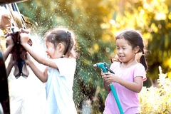 Deux filles asiatiques d'enfant ayant l'amusement à aider à parent la voiture de lavage photos stock