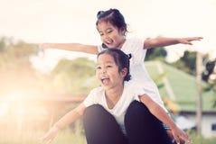 Deux filles asiatiques d'enfant ayant l'amusement à voler sur la jambe du ` s de mère Photos libres de droits