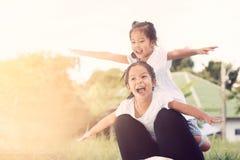 Deux filles asiatiques d'enfant ayant l'amusement à voler sur la jambe du ` s de mère Photographie stock