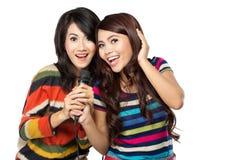 Deux filles asiatiques dans le T-shirt rayé chantant ensemble Photographie stock