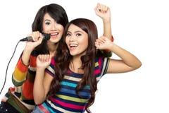Deux filles asiatiques dans le T-shirt rayé chantant ensemble Photographie stock libre de droits