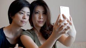 Deux filles asiatiques de métis prenant le selfie avec le téléphone intelligent Images libres de droits