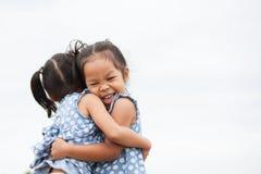 Deux filles asiatiques heureuses d'enfant s'étreignant avec amour Photographie stock