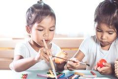 Deux filles asiatiques mignonnes d'enfant dessinant et peignant sur l'oeuf de pâques Photographie stock libre de droits