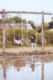 Deux filles asiatiques mignonnes d'enfant jouant des oscillations ensemble dans la ferme Photo libre de droits