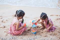 Deux filles asiatiques mignonnes de petit enfant ayant l'amusement à jouer avec le sable Photo libre de droits