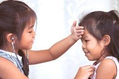Deux filles asiatiques mignonnes de petit enfant jouant le docteur et le patient Photo stock