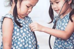 Deux filles asiatiques mignonnes de petit enfant jouant le docteur et le patient Photographie stock libre de droits