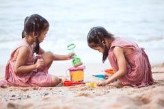 Deux filles asiatiques mignonnes de petit enfant jouent avec le sable sur la plage Image stock