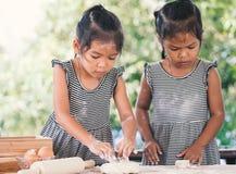 Deux filles asiatiques mignonnes de petit enfant préparent une pâte pour la cuisson photographie stock libre de droits