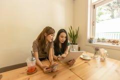 Deux filles asiatiques utilisent un comprimé tout en se reposant dans un café et un café potable Photos libres de droits