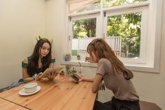 Deux filles asiatiques utilisent un comprimé tout en se reposant dans un café et un café potable Image libre de droits