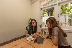 Deux filles asiatiques utilisent un comprimé tout en se reposant dans un café et un café potable Image stock
